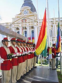 la tricolor en primer plano es izada frente al Palacio Quemado