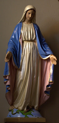 Window lit statue of Mary standing on the world with a serpent under her foot.