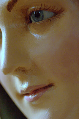 Close up of Saint Therese statue's face detailing her glass eye