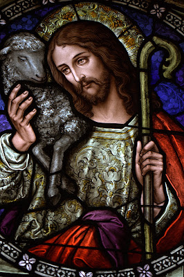 Stained glass window of Jesus the Good Shepherd with a lamb on his shoulder
