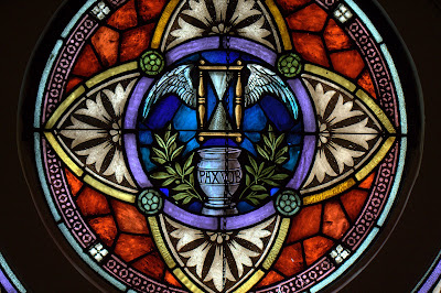 Close up of stained glass window of hourglass with wings