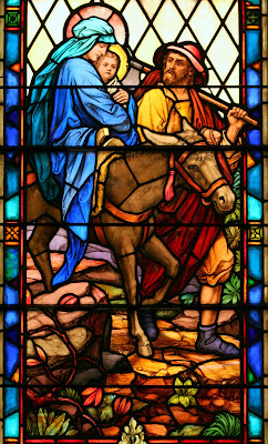 Full pane stained glass window with Mary, Joseph, Jesus and Donky fleeing to Egypt
