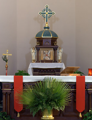 High Alter with red sashes and palms