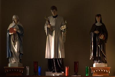 Window lit statues of three saints