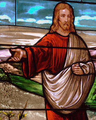 Close up of stained glass window of Jesus sowing seeds.