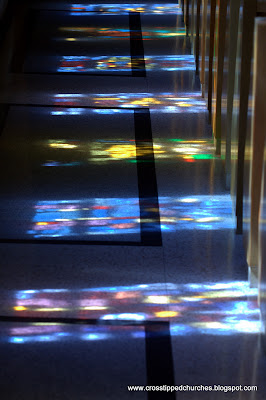 Reflection of stained glass windowds on tiled floor and side of pews.