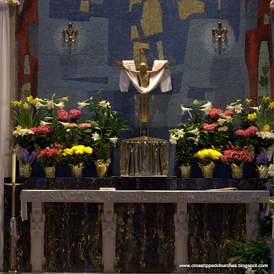 High Alter decorated for Easter with modern crucifix hanging above.