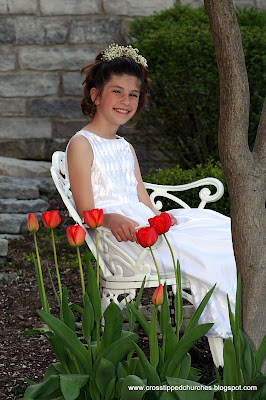Emily in white Communion dress sitting on white bench with tulips.