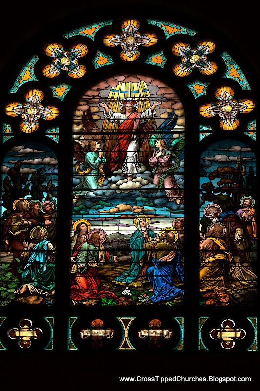 Large stained glass window of the resurrected Christ in the clouds with angels,and the deciples and Mary below.