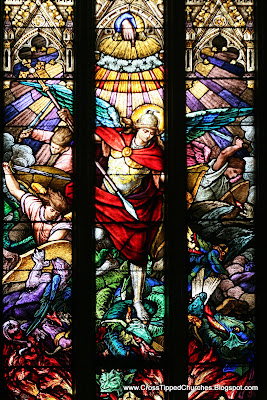 Very colorful stained glass widdow of the the Arch Angel MIchael in battle againes Satan.