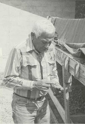 Fig. 7 - Anthony Davis, a Pawnee Road Chief, examining drying peyote 'buttons.'