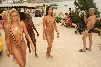 Two bikini dare models wearing slings around public beaches.