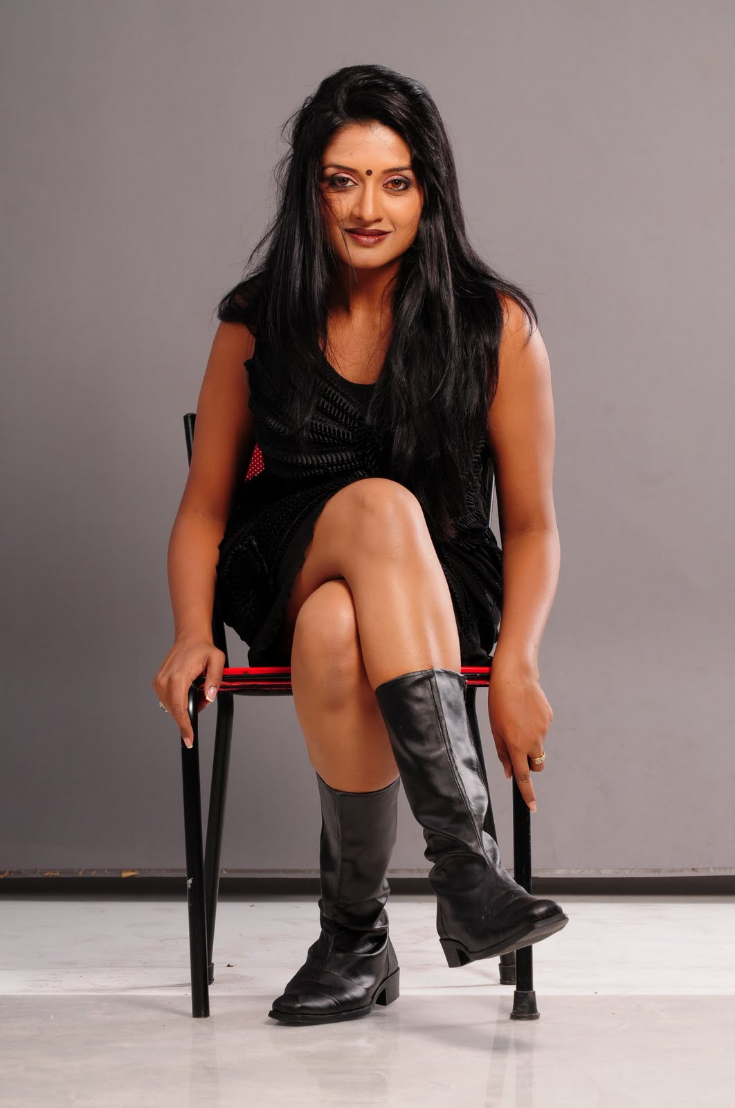 Vimala Raman in sitting in chair with crossed legs and High Black Boots
