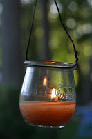 weck canning jar used as a lantern in green twilight garden