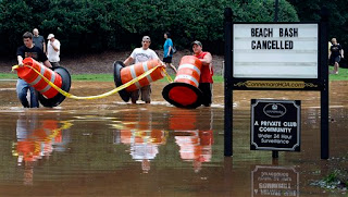 From left: Garrett Jacobs, Dakota Nelson, and Levi Wright move a barricade to higher ground after flood waters from the Yellow River continued to rise Monday, Sept. 21, 2009 in Lilburn. Ga. The community canceled their beach bash, which was scheduled for Monday night. (AP Photo/Atlanta Journal-Constitution, Curtis Compton)
