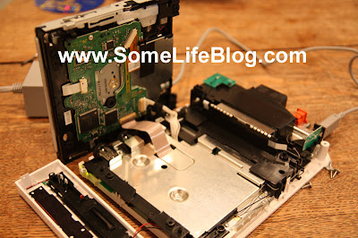 Nintendo Wii DVD Drive Repair: Set the DVD drive on its side next to the Wii, leaving it still attached to the Nintendo Wii, as per the picture below.  You will need to connect the power to your Wii.