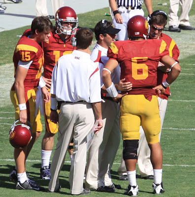 Steve Sarkisian strategizes the next offensive pay with Mark Sanchez while Mitch Mustain and Aaron Corp listen in.