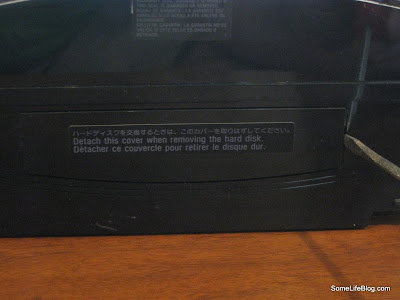 Sony PS3 Playstation 3: Find the side of your PS3 with the sticker labeled Detach this conver when removing the hard disk.  There is a little tab on the right hand side.  Place your flat head screwdrived in the slot and slide the plastic piece.  It should snap and then pop right out.