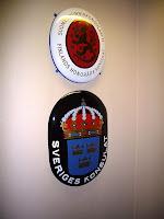 Suomen ja Ruotsin vaakunat seinällä sulassa sovussa konsulaatin oven vieressä.