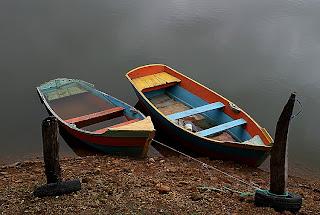duas canoas ancoradas na margem de um rio