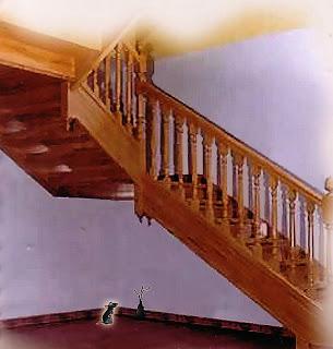 ratinho debaixo da escada olhando para o buraco na parede