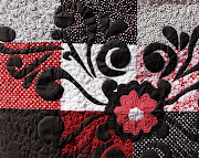 . circle on the white, and echo quilting on the red and black petals.