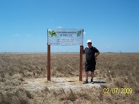Posting sign of new planting area on very hot day