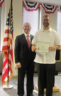 Erick Lopez, right, receives the first new Certificate of Naturalization from Director Mayorkas in Baltimore