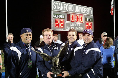 BYU Rugby coaches, Tarawhiti, Smyth, Kjar, and Nadauld, come together with the coveted trophy and scoreboard