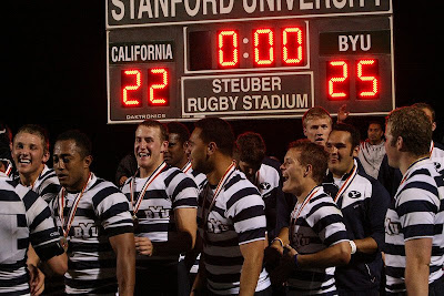 The BYU Rugby team gathers near the scoreboard for pictures with their gold medals