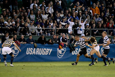 Center Tupu Folau stiff-arms a Cal defender as BYU fans look on intently