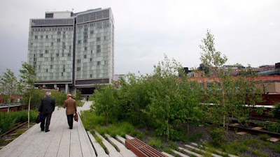 People walk on an abandoned elevated rail line that became a public park called The High Line, with the Standard Hotel in the background, in New York on Monday, June 8, 2009. (AP / Richard Drew)