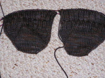 two knitted sock-toes on circular needles in dark brown yarn