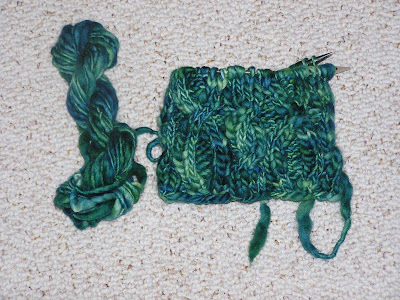 an unfinished knit cable hat, still on the needles