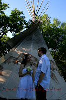 couple standing in front of tipi