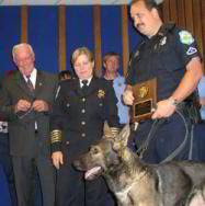 Officer Michael Erwin and his K-9 partner, Banook, display a plaque received from Chief Dorene Thomas. Photo Credit: Julie Roberts
