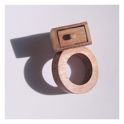 Chunky wooden ring with an offset miniature drawer on the top.