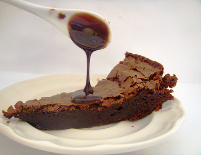 Spoon pouring sauce on chocolate cake.