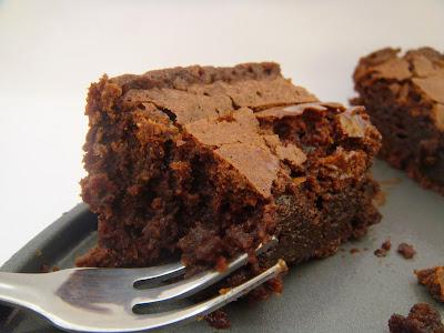 Fork cutting into chocolate cake.