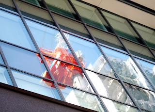 Gru riflessa sul grattacielo