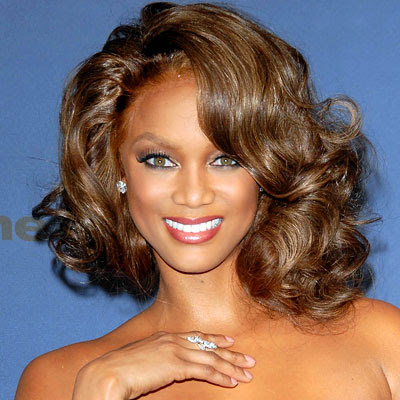 Tyra Banks favors long hair styles and combines them with braids and hair