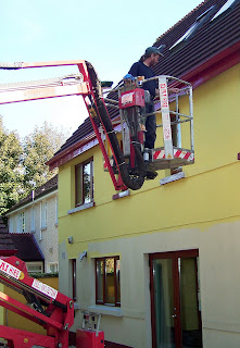 man house painting, using cherry picker to reach the windowsills on the second floor