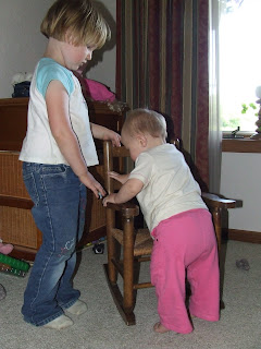 Harmony sharing her rocking chair and helping Sierra get up into the seat