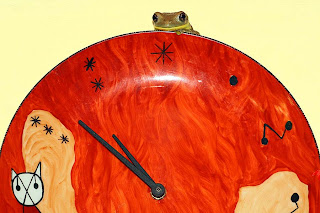 a tree frog watches the world go by from behind the kitchen clock