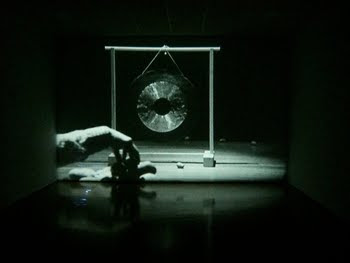 una imagen de la obra de Rodney Graham Lobbing Potatoes at a gong 1969
