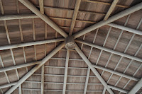 A picture of the ceiling of a wooden gazebo we went and sat at later on. It's wood and is laid out in the pattern of a star burst. It used 2 by 6 inch wooden slats to make the whole thing. I'm guessing those dimensions lol