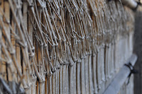 This is a close up of a fence made out of little sticks, it's kind of japanese themed