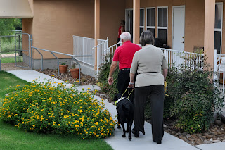 A client with her guide and a board member making their way down a sidewalk into the client living area