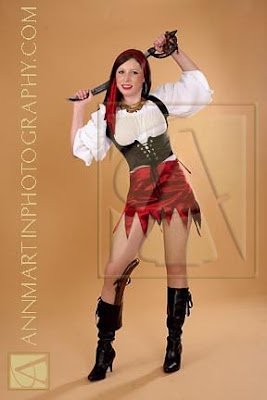 full length picture of home made pirate girl costume or pirate wench with sword and gun and jewelry and headscarf