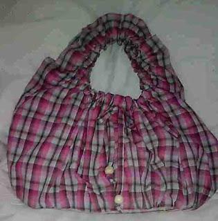 Bonito bolso juvenil elaborado en tela a cuadros rosada, con agarradera con elástico. Forrado por dentro y con bolsillo interior.